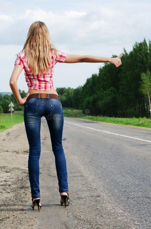 La muchacha en pantalones vaqueros para el coche en el camino imagen de archivo