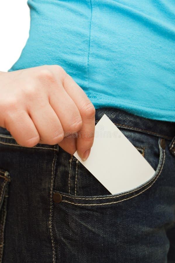 La muchacha en pantalones vaqueros sostiene la tarjeta de papel fotografía de archivo