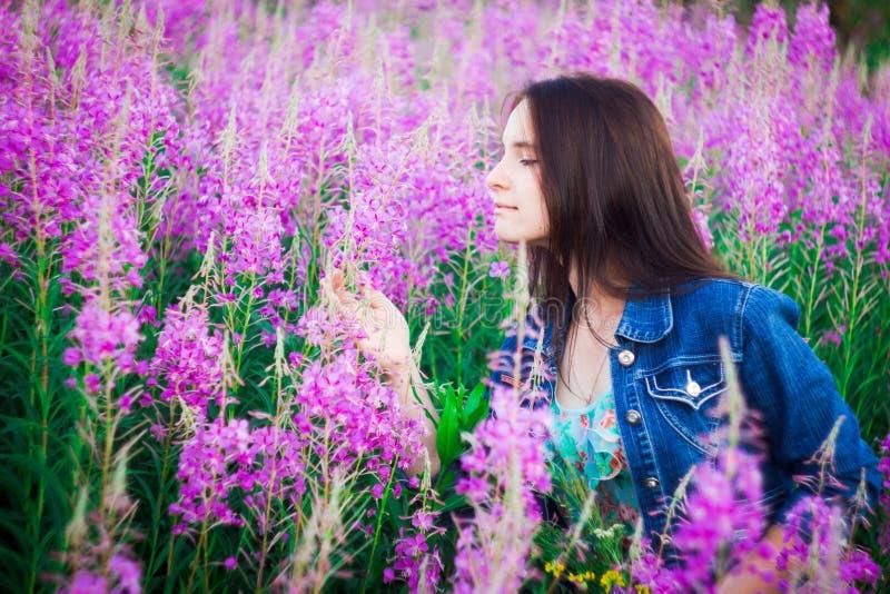 La muchacha en perfil en un fondo de los prados púrpuras de la flor con una sonrisa que mira las flores foto de archivo