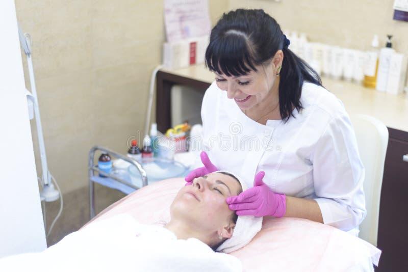 La muchacha en la recepción en el cosmetólogo hace el limpiamiento facial imagen de archivo