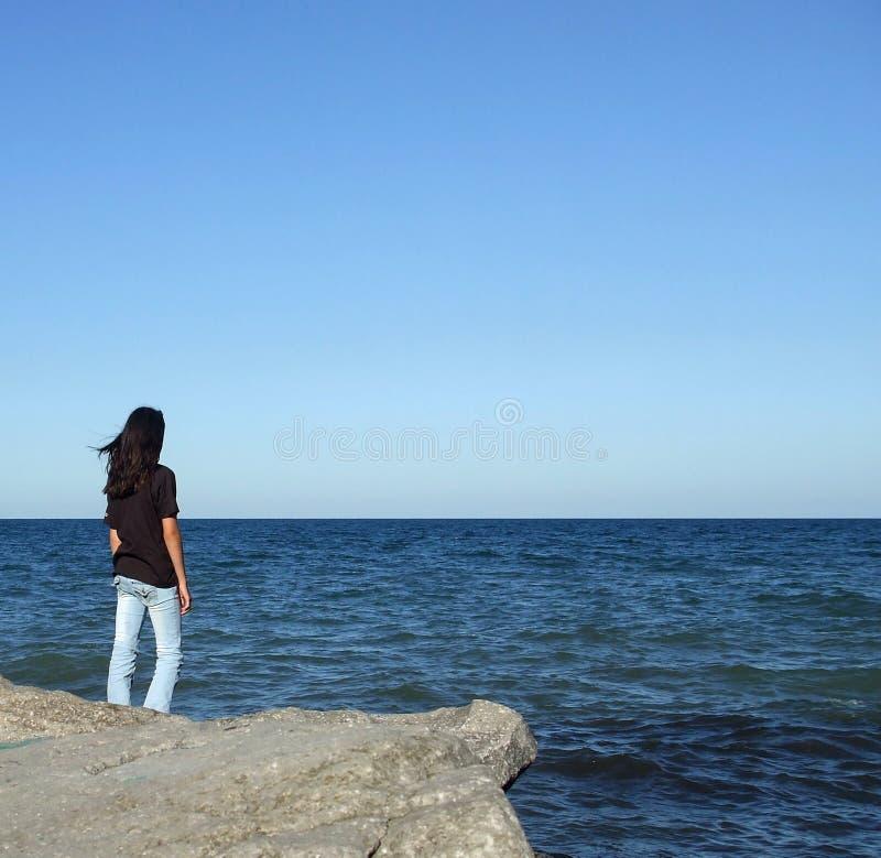 La muchacha en roca mira el agua fotos de archivo libres de regalías