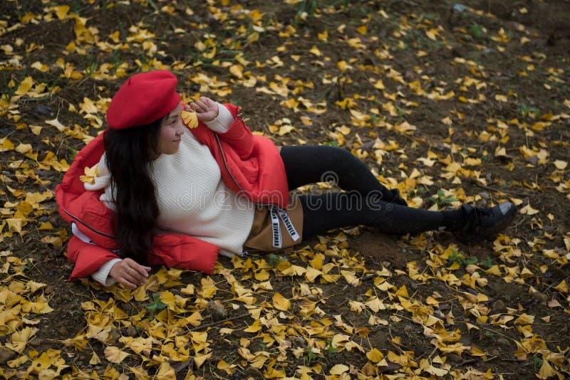 La muchacha en rojo cubre con la hoja del ginkgo imagen de archivo