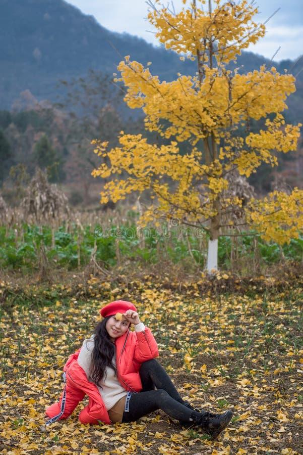 La muchacha en rojo cubre con la hoja del ginkgo foto de archivo libre de regalías