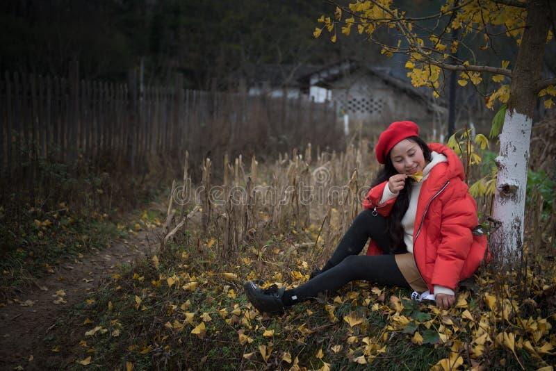 La muchacha en rojo cubre con la hoja del ginkgo imágenes de archivo libres de regalías