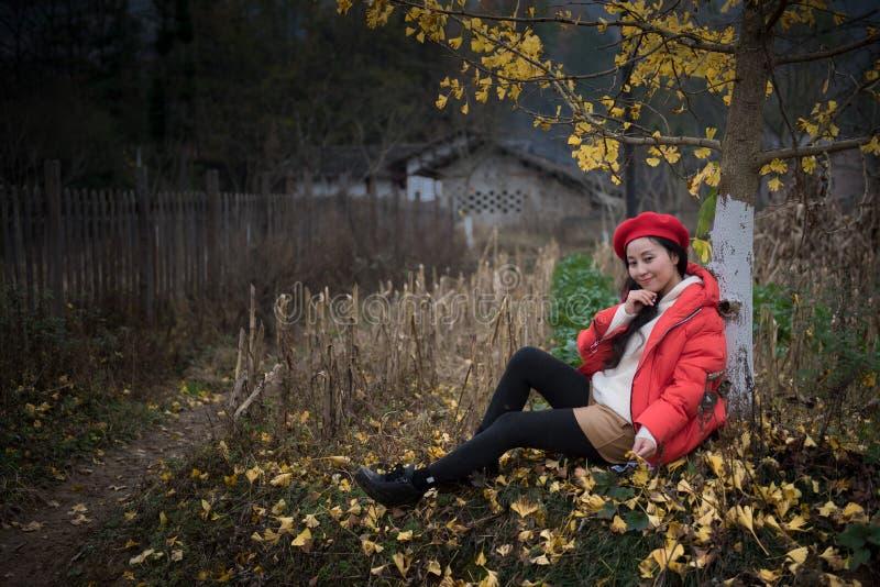 La muchacha en rojo cubre con la hoja del ginkgo fotos de archivo