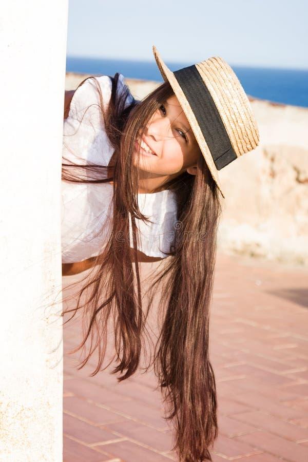 La muchacha en sombrero de paja mira a escondidas hacia fuera de detrás la pared imagenes de archivo