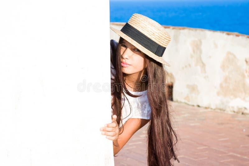 La muchacha en sombrero de paja mira a escondidas hacia fuera de detrás la pared imagen de archivo