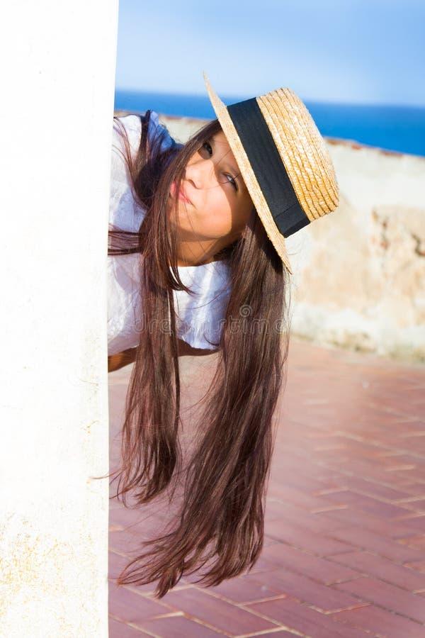 La muchacha en sombrero de paja mira a escondidas hacia fuera de detrás la pared fotografía de archivo libre de regalías