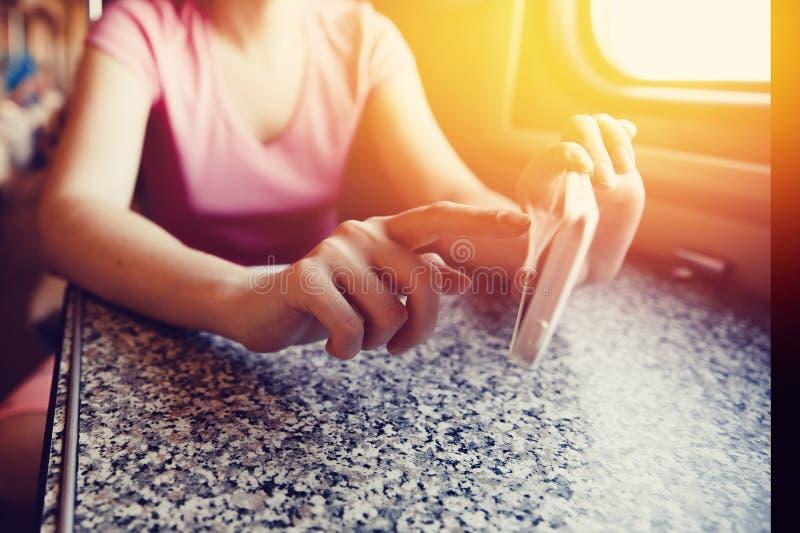 La muchacha en sus manos sostiene un teléfono móvil y empuja su finger en el viaje en tren y tren en el coche imagenes de archivo