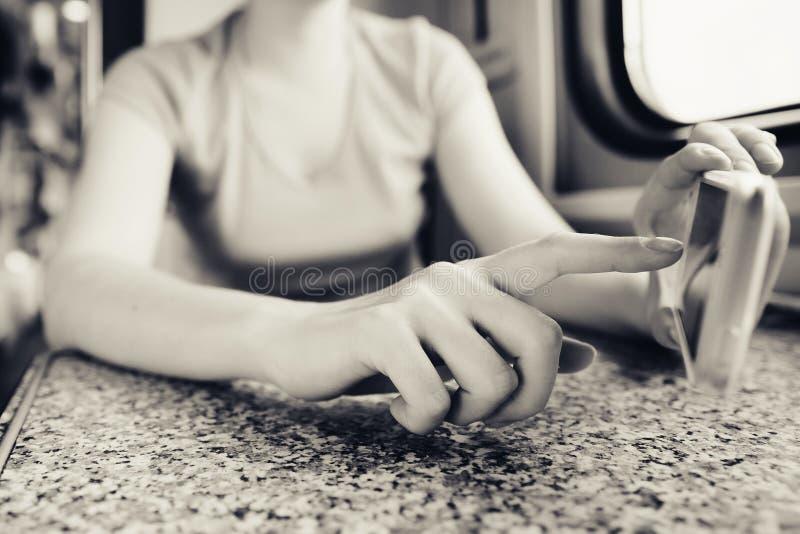 La muchacha en sus manos sostiene un teléfono móvil y empuja su finger en el viaje en tren y tren en el coche imagen de archivo