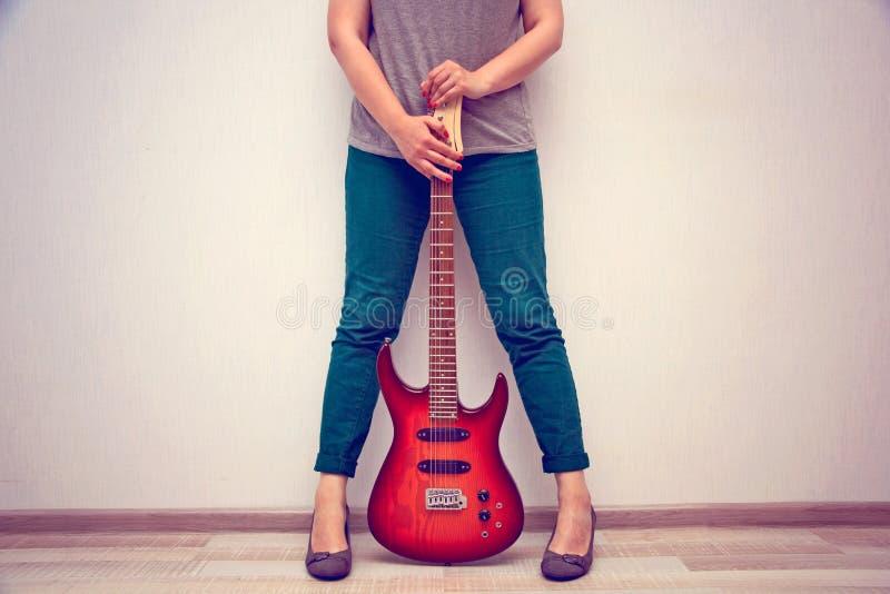 La muchacha en tacones altos se opone a la pared y sostiene la guitarra eléctrica fotografía de archivo