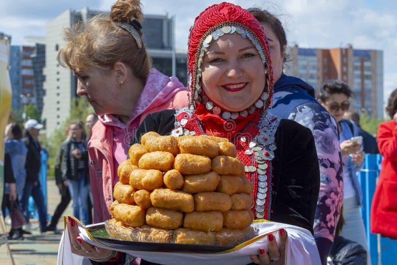 La muchacha en traje bashkir nacional lleva un plato 'CHAK-CHAK 'en una bandeja, vista delantera foto de archivo