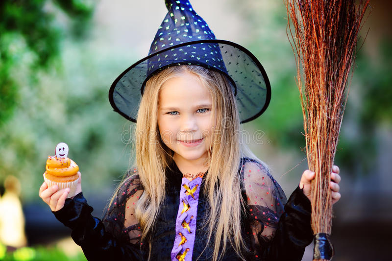 La muchacha en traje de la bruja come la magdalena en Halloween foto de archivo libre de regalías