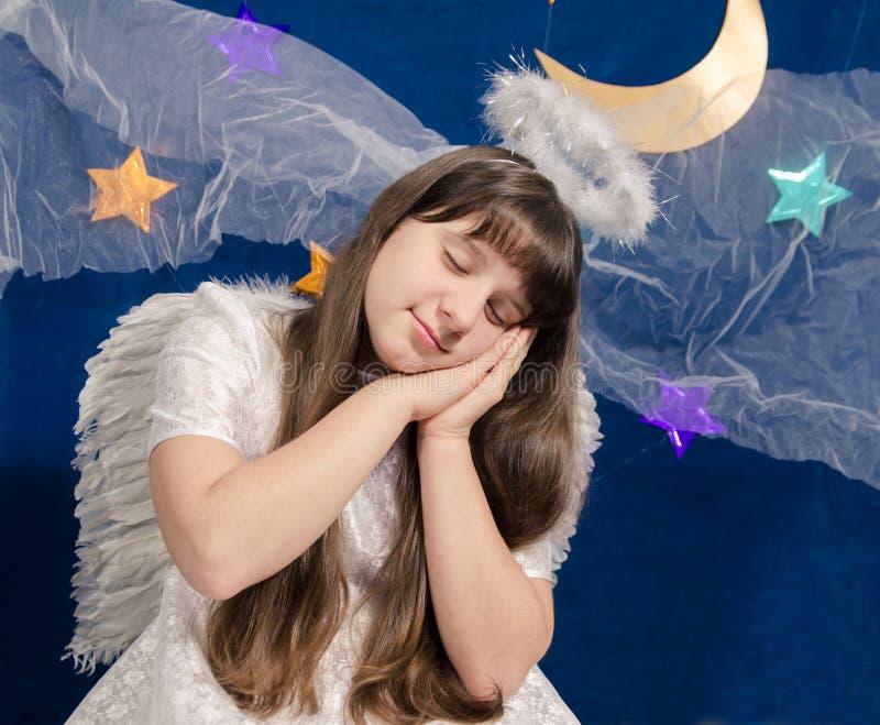 La muchacha en traje del ángel duerme en un fondo del cielo azul marino fotografía de archivo