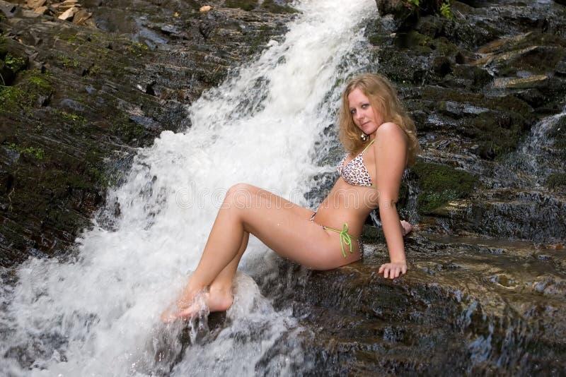 La muchacha en un bikiní en rocas en un Mingo se cae. imagen de archivo