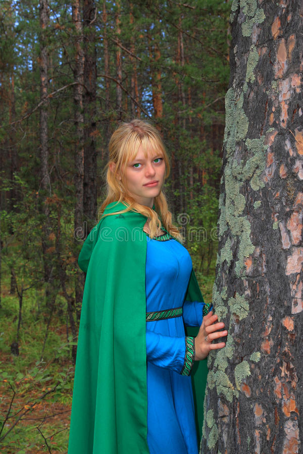 La muchacha en un impermeable verde sobre un pino imagen de archivo
