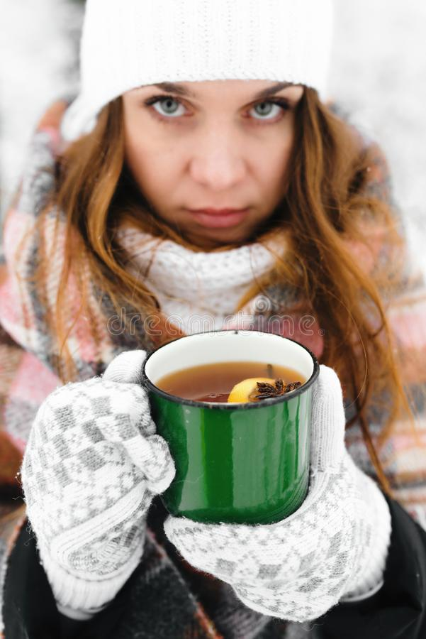 La muchacha en un sombrero blanco envuelto en una manta sostiene una taza de té en invierno fotografía de archivo