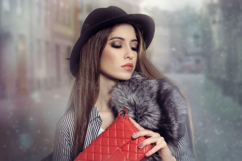 La muchacha en un sombrero negro camina a través de las calles de niebla de la ciudad fotos de archivo libres de regalías
