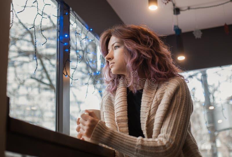 La muchacha en un suéter blanco se sienta en un café y mira hacia fuera la ventana imagen de archivo libre de regalías