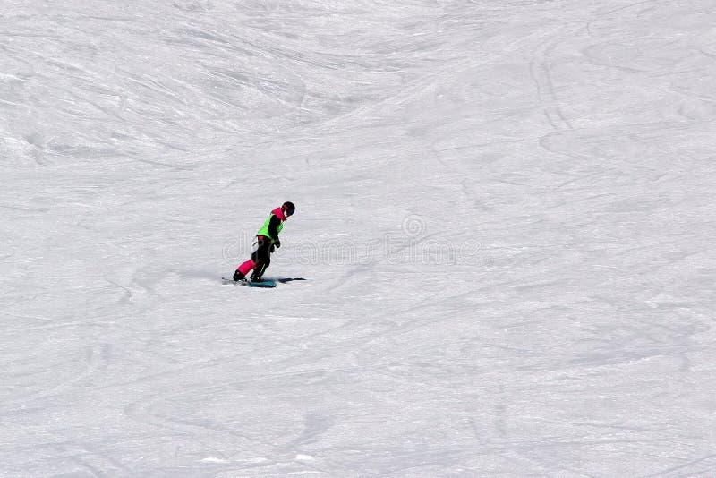 La muchacha en un traje colorido está en paseos de una snowboard con las montañas fotografía de archivo libre de regalías