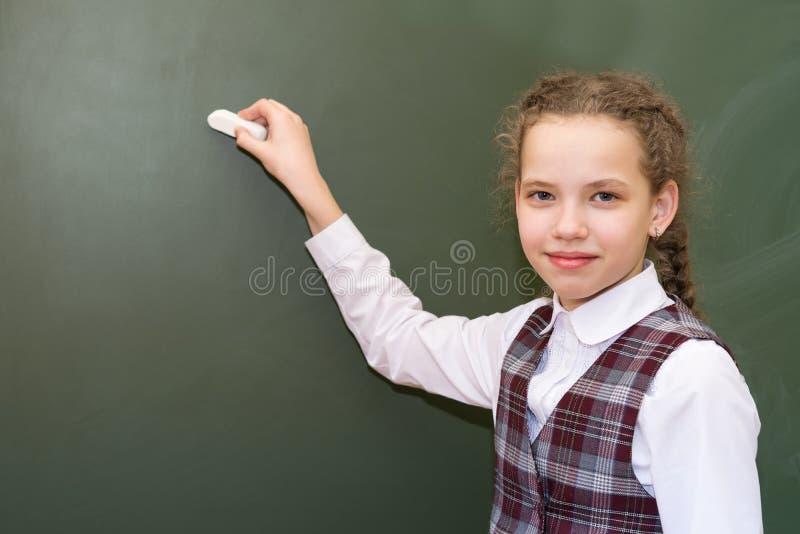 La muchacha en un uniforme escolar se está colocando delante de un tablero verde foto de archivo libre de regalías