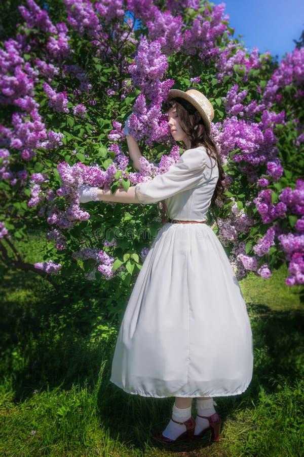 La muchacha en un vestido blanco abraza una lila floreciente imagenes de archivo