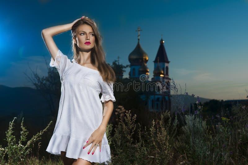 La muchacha en un vestido blanco en el campo contra el churc ruso foto de archivo libre de regalías
