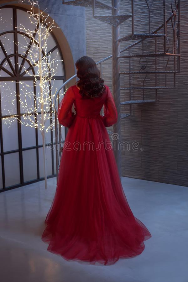 La muchacha en un vestido largo lujoso rojo delicioso con ella de nuevo a la cámara, demuestra el pelo oscuro con las ondas perfe imagen de archivo