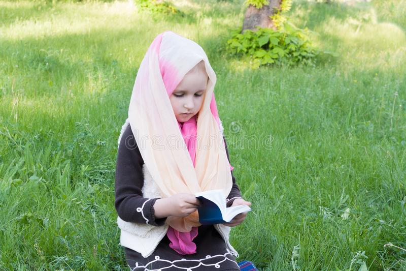 La muchacha en una bufanda El estudiar de la biblia en el aire fresco fotos de archivo