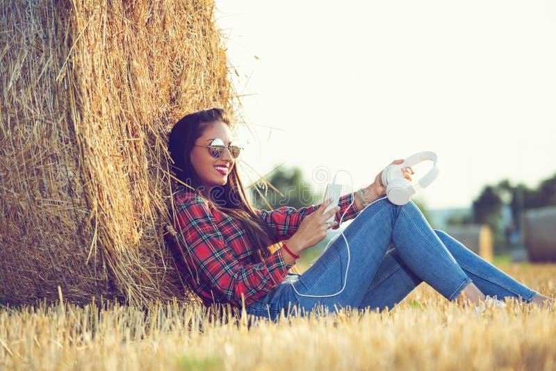 La muchacha en una camisa de tela escocesa roja se está sentando en el campo, mirando su teléfono foto de archivo libre de regalías