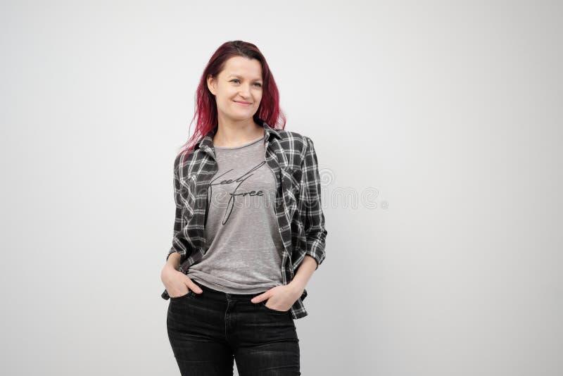 La muchacha en una camisa gris de la tela escocesa en un fondo blanco con el pelo rojo teñido imágenes de archivo libres de regalías