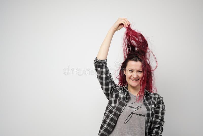 La muchacha en una camisa gris de la tela escocesa en un fondo blanco con el pelo rojo teñido imagen de archivo libre de regalías