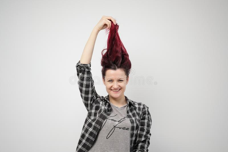 La muchacha en una camisa gris de la tela escocesa en un fondo blanco con el pelo rojo teñido imagen de archivo