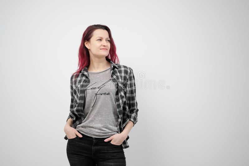 La muchacha en una camisa gris de la tela escocesa en un fondo blanco con el pelo rojo teñido fotos de archivo libres de regalías