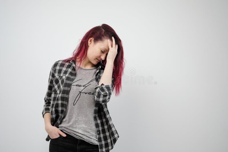 La muchacha en una camisa gris de la tela escocesa en un fondo blanco con el pelo rojo teñido imagenes de archivo