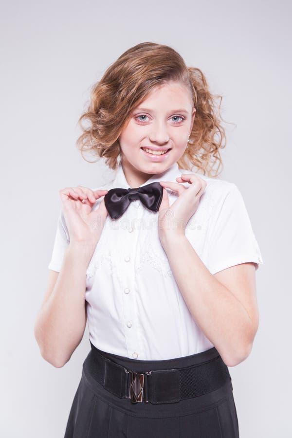La muchacha en una camisa y una corbata de lazo blancas mira la cámara y el smilin imágenes de archivo libres de regalías