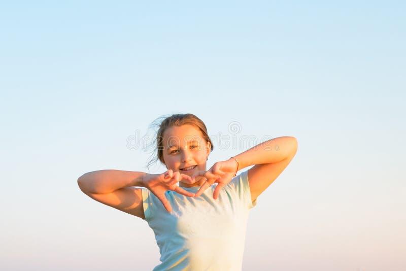 La muchacha en una camiseta azul muestra su corazón con su fingerst imagen de archivo