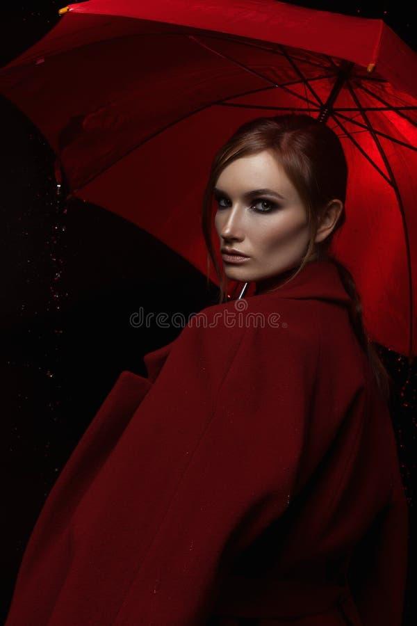 La muchacha en una capa roja con un paraguas rojo en la lluvia imagenes de archivo