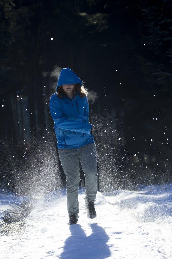 La muchacha en una chaqueta azul con la capilla con la capilla en corre fuera de las FO oscuras fotos de archivo libres de regalías
