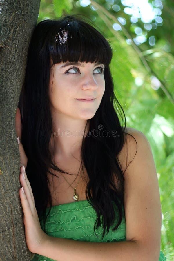 La muchacha en una cortina del árbol fotos de archivo libres de regalías