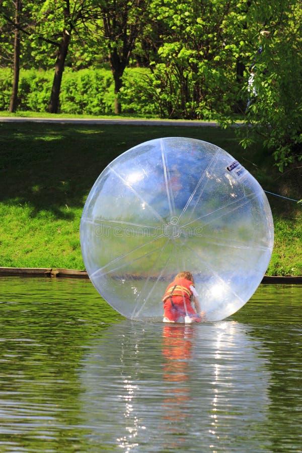 La muchacha en una esfera transparente imagenes de archivo