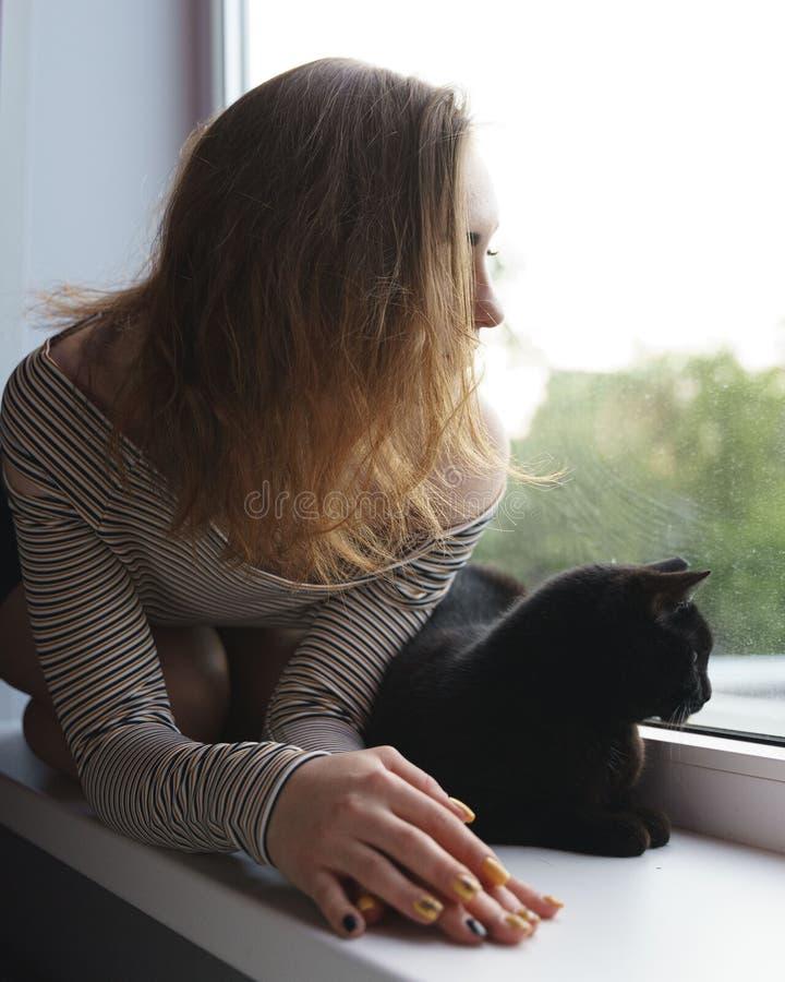 La muchacha en una falda y un gato se están sentando en la ventana en la tarde de la calle imagen de archivo libre de regalías