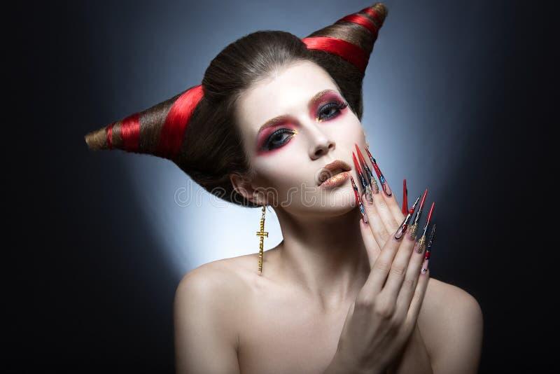 La muchacha en una imagen del demonio-tentador con los clavos largos y del corte de pelo bajo la forma de cuernos imagenes de archivo