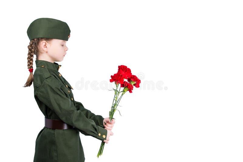 la muchacha en uniforme se está colocando de lado con un ramo de flores rojas, en un fondo blanco imagen de archivo libre de regalías