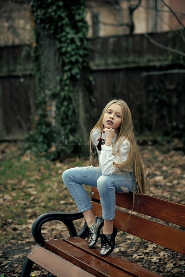 La muchacha en vaqueros de moda se sienta en el banco, moda Pequeño niño con el pelo rubio largo, belleza al aire libre del peina imágenes de archivo libres de regalías