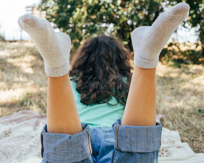La muchacha en vaqueros y una camiseta miente en un prado en el parque y la lectura de un libro imagen de archivo