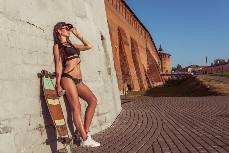 La muchacha en verano en la ciudad, un monopatín del longboard, coloca en su mano una botella de agua, espacio libre para el text fotografía de archivo