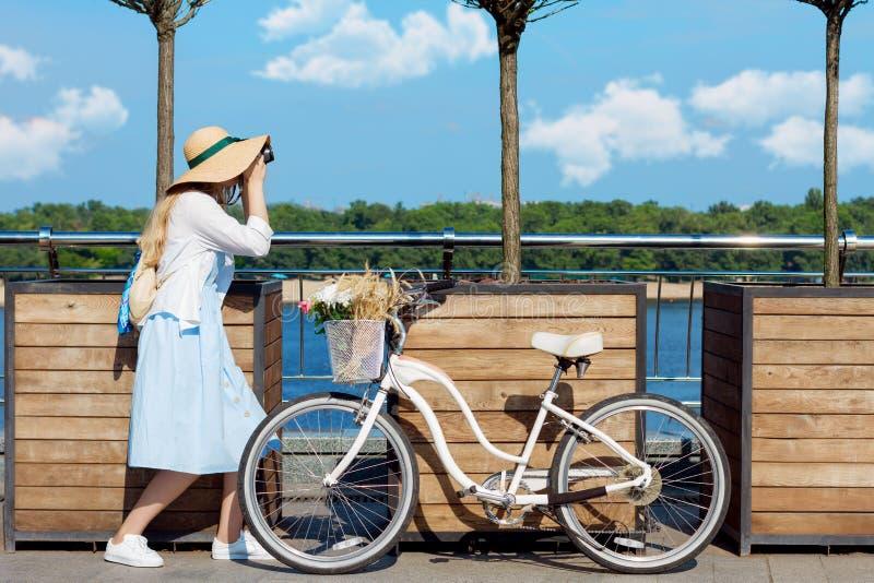 La muchacha en vestido azul y el sombrero de moda toman una imagen cerca de la bicicleta foto de archivo