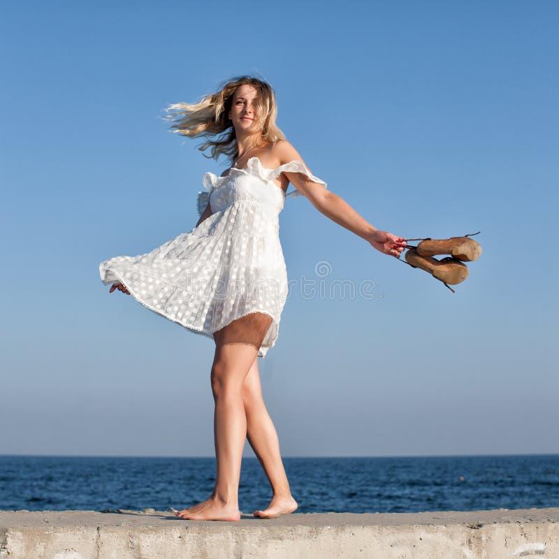 La muchacha en vestido sin mangas blanco corto gira con el zapato en su Han imagen de archivo