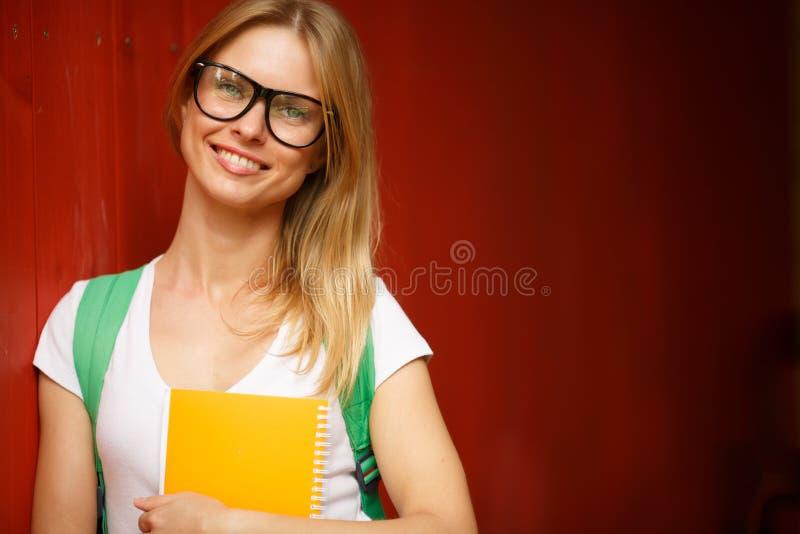 La muchacha en vidrios sonríe en medio de la pared de madera de Borgoña imagen de archivo
